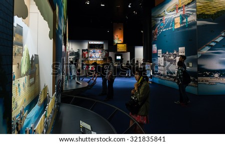 OSAKA, JAPAN - SEPTEMBER 21, 2015: Visitors look at an exhibit in the Osaka Museum of History.