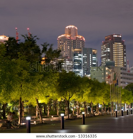 Osaka skyline in the background with trees in the foreground in the evening - stock photo