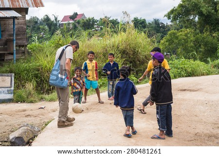 Osango, Indonesia - August 17, 2014: Group of unidentified funny children of indonesian ethnicity playing football with adult european man in the village of Osango, Mamasa region, Sulawesi, Indonesia. - stock photo