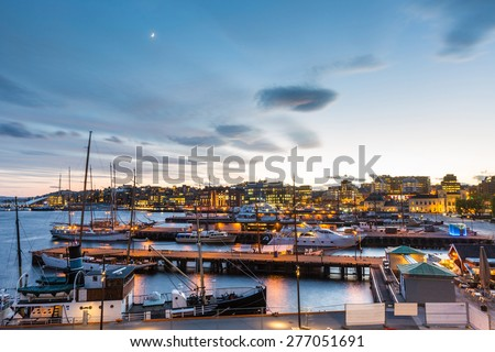 Oslo harbour with boats and yachts at twilight. There are both private and touristic boats, and on background some modern buildings. - stock photo