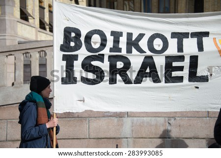 "OSLO - MARCH 30: Activists hold a banner reading ""Boycott Israel"" during a protest in front of the Norwegian Parliament building, Oslo, March 30, 2015.  - stock photo"