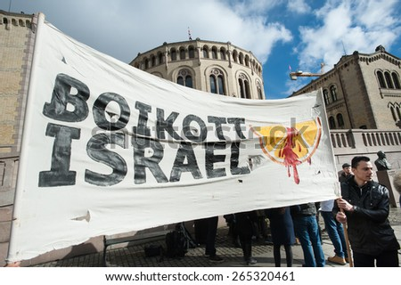 "OSLO - MARCH 30: Solidarity activists hold a banner reading ""Boycott Israel"" during a protest in front of the Norwegian Parliament building, Stortinget, Oslo, March 30, 2015.  - stock photo"