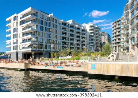OSLO, NORWAY - AUGUST 13: Environment in modern district with sunbathing young people on man-made beach in warm day on August 13, 2015 in Oslo, Norway - stock photo