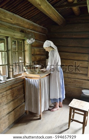 OSLO, NORWAY - JULY 11, 2016: Norwegian Museum of Cultural History. Young woman  in old wooden house prepares dough for lefse