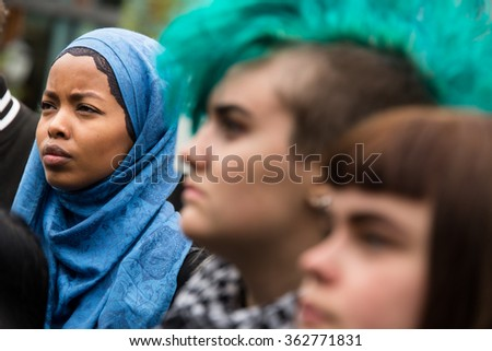 OSLO - SEPTEMBER 12: A Muslim woman wearing a hijab headscarf stands side by side with a punk woman with a green mohawk at a rally in support of Syrian refugees, Oslo, Norway, September 12, 2015. - stock photo