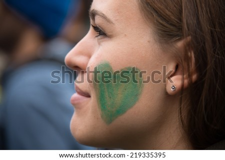 OSLO - SEPTEMBER 21: A woman has a green heart painted on her face as thousands march through downtown Oslo, Norway, to support action on global climate change, September 21, 2014.  - stock photo