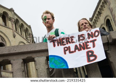 "OSLO - SEPTEMBER 21: Men hold a sign reading, ""There Is No Planet B"", as thousands march through downtown Oslo, Norway, to support action on global climate change, September 21, 2014.  - stock photo"