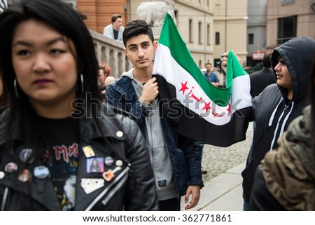 OSLO - SEPTEMBER 12: Young men hold a Syrian flag at a rally in support of Syrian refugees in front of the parliament building in Oslo, Norway, September 12, 2015. - stock photo