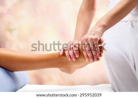Osteopath doing reflexology massage on female foot against colorful background.