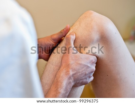Osteopath's hands working on the patient's knee during an osteopathic treatment.