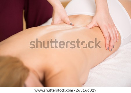 Osteopath treating painful back of young woman