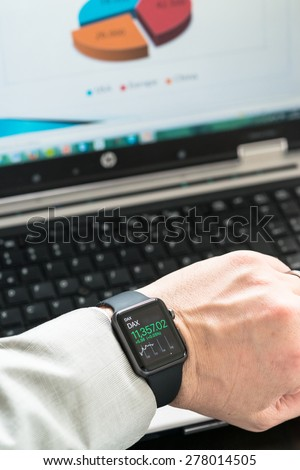 OSTFILDERN, GERMANY - MAY 14, 2015: A businessman is checking stock market prices using his black Apple Watch Sport while creating a presentation on his laptop computer. The Apple Watch is the latest - stock photo