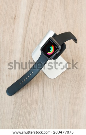 OSTFILDERN, GERMANY - MAY 21, 2015: An Apple Watch Sport 42mm with space gray aluminium case and black sport band displaying mediocre daily activity on its screen in a stylish stand by manufacturer - stock photo