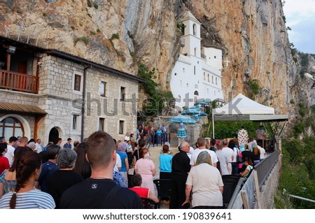 OSTROG, MONTENEGRO - JULY 20: faithful attend the religious ceremony officiated in front of the white church of Ostrog Monastery, a stunning place of pilgrimage for Orthodox Christians. Shot on 2013 - stock photo