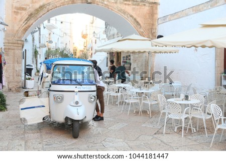 OSTUNI, ITALY - MAY 29, 2017: People ride weird Italian Piaggio tricycle to tour Ostuni Old Town in Italy. Ostuni is a major tourism destination in the region of Apulia, and has a big expat community.