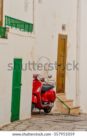 OSTUNI, ITALY - SEPTEMBER 2015: Red traditional Vespa on the streets of Ostuni, as seen in September 2015.