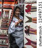 OTAVALO, AUGUST 4, 2012: Indian women in national clothes sells the products of her weaving, as usual on weekdays on the most famous markets in South America, on August 4, 2012 in Otavalo, Ecuador - stock photo