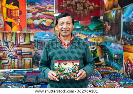 Otavalo, Ecuador, August 30, 2014: Indigenous Ecuadorian artist from Sierra region presenting traditional colorful and decorative paintings on sheepskin canvases. Picture taken at the Otavalo Market. - stock photo