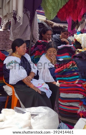 OTAVALO, ECUADOR - FEBRUARY 13, 2016: Indigenous women in traditional dress at a stall in the market