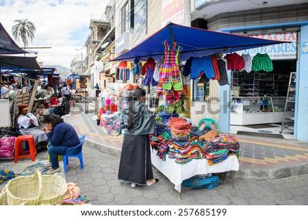 OTAVALO, ECUADOR - JAN 3, 2015: Unidentified Ecuadorian woman in traditional clothes works at the Otavalo Market. 71,9% of Ecuadorian people belong to the Mestizo ethnic group - stock photo