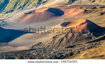 Otherworldly Volcanic landscape with colorful cinder cones inside the crater at the summit of Haleakala volcano at sunrise on the island of Maui, hawaii.  - stock photo