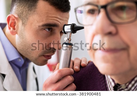 Otologist examining senior patient ear - stock photo