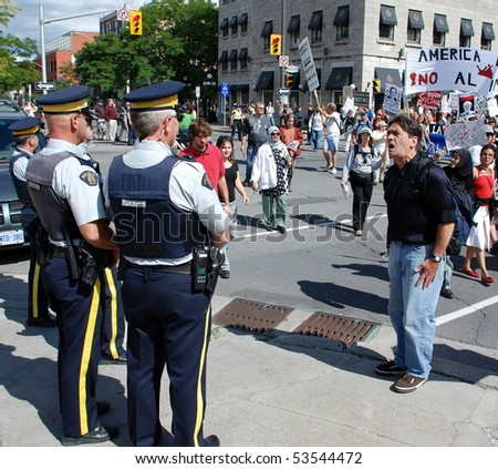 OTTAWA - AUG. 19: Protester hollers at 2 Royal Canadian Mounted Police during the protest of the Security and Prosperity Partnership talks in Ottawa, Canada on Aug. 19, 2007.
