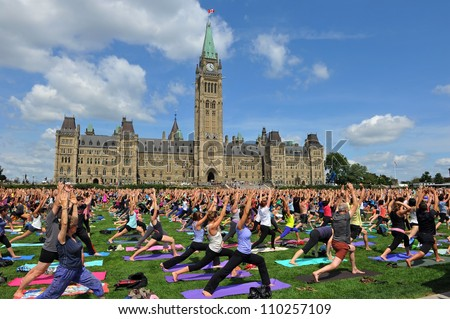 OTTAWA, CANADA – AUG 15:  For the past six years people have gathered on Parliament Hill at lunch on Wednesdays to do yoga.  A new record was set when 2400 participated August 15, 2012 Ottawa, Canada. - stock photo
