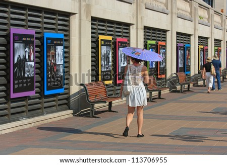 OTTAWA, CANADA - AUGUST 25: A woman passing an outdoor exhibit at the Chateau Laurier Hotel on August 25, 2012 in downtown Ottawa, Ontario. The exhibit was in honor of the Queen's Diamond Jubilee. - stock photo