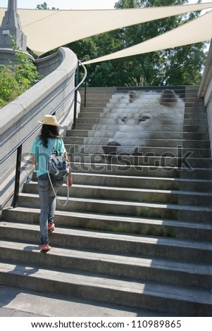 OTTAWA, CANADA - AUGUST 4: An unidentified woman walks among part of the National Capital Commission's Eco Art exhibit at the Plaza Bridge Terrace on August 4, 2012 in downtown Ottawa, Ontario. - stock photo