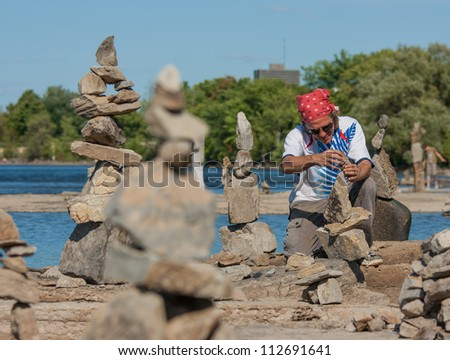 OTTAWA, CANADA - AUGUST 18: Dan Davis of Canada balances stones while participating in the  International Stone Balance Festival on August 18, 2012 at Remic Rapids in Ottawa, Ontario. - stock photo