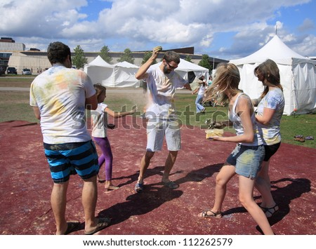 OTTAWA, CANADA -Â?Â? AUGUST 12: People throwing colored powders during holi at the Festival of India on August 12, 2012 in Ottawa, Ontario. Holi is like a game of tag but uses colored powders and water. - stock photo
