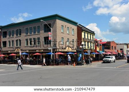 OTTAWA, CANADA - AUGUST 8, 2014:  The Byward Market in Ottawa continuously draws tourists and locals to its many pubs and restaurant such as the ones pictured above on the busy Clarence Street. - stock photo