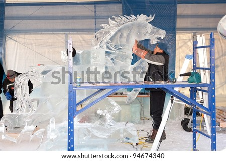 OTTAWA, CANADA - FEB 4: Ice sculptors at work during the famous annual Winterlude Festival on February 4, 2012 in Ottawa, Ontario, Canada. - stock photo