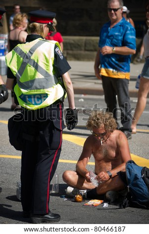 OTTAWA, CANADA - JULY 1: A female Police Officer confronts an unidentified, shirtless man on Wellington street during the July 1st, 2011 Canada Day celebrations in Ottawa, Ontario Canada. - stock photo