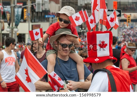 OTTAWA, CANADA - JULY 1: A man buying Canadian flags for his family during Canada Day on July 1, 2013 in downtown Ottawa, Ontario. - stock photo