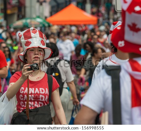 OTTAWA, CANADA - JULY 1: An Asian girl trying to catch a photo during Canada Day on July 1, 2013 in downtown Ottawa, Ontario.