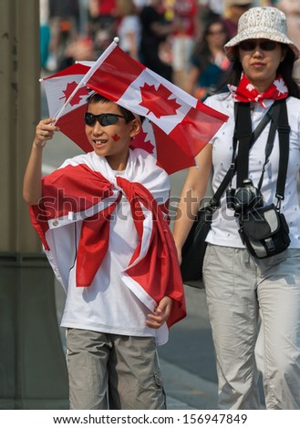OTTAWA, CANADA - JULY 1: An unidentified Asian boy waving a Canadian flag during Canada Day on July 1, 2013 in downtown Ottawa, Ontario.