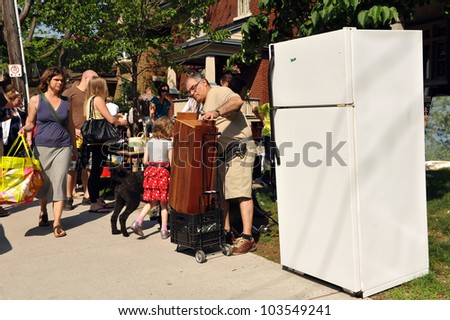 OTTAWA, CANADA - MAY 26: Thousands of people gather at the annual Glebe neighborhood garage sale which takes place for several blocks in the Glebe area of Ottawa, Ontario May 26, 2012. - stock photo