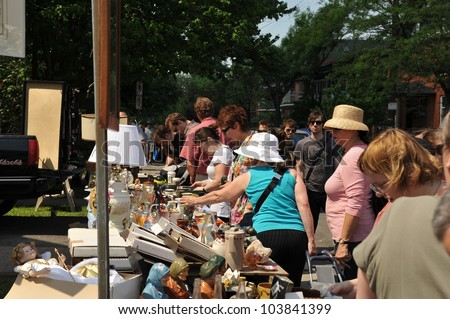 OTTAWA, CANADA - MAY 26: Thousands of people gather at the annual Glebe neighborhood garage sale which takes place for several blocks May 26, 2012 in the Glebe area of Ottawa, Ontario. - stock photo