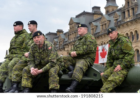 OTTAWA - MAY 9:  Soldiers who served in the Canadian Forces in Afghanistan sit on armoured vehicle while being honored on Parliament Hill during national Day of Honour May 9, 2014 in Ottawa, Canada - stock photo