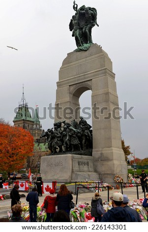 OTTAWA - OCT 25, 2014: Mourners gather and leave flowers at the Cenotaph in Ottawa, where guard Nathan Cirillo was shot 3 days before.  Parliament Hill, with the flag half mast, is visible in picture. - stock photo