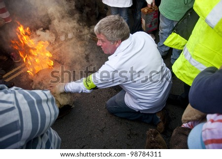 OTTERY - NOVEMBER 5: A carnival committee member lights the tar barrel at the start of the 2011 Tar Barrels of Ottery Carnival  on November 5, 2011 in Ottery St Mary, UK.