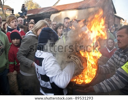OTTERY ST MARY -  NOVEMBER 5: A young roller attempts to pick up a burning tar barrel at the start of the 2011 Tar Barrels of Ottery Carnival on  November 5, 2011 in Ottery St Mary