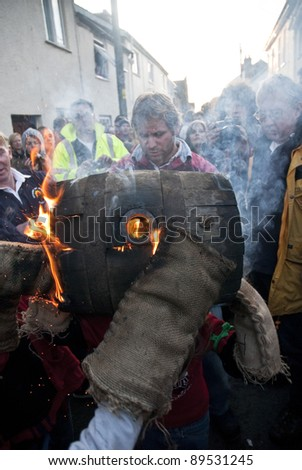 OTTERY ST MARY -  NOVEMBER 5: Flaming gloves as two young barrel roller exchange a burning barrel at the 2011 Tar Barrels of Ottery Carnival  on  November 5, 2011 in Ottery St Mary