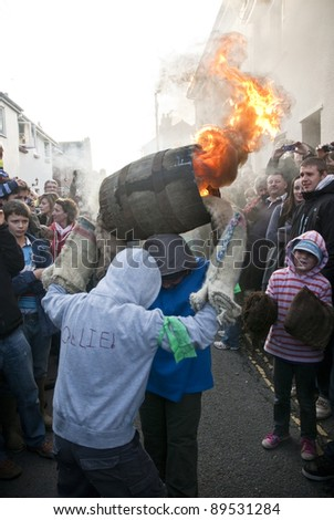 OTTERY ST MARY -  NOVEMBER 5: Two young barrel rollers exchange a burning barrel at the 2011 Tar Barrels of Ottery Carnival on Sandhill Street  on  November 5, 2011 in Ottery St Mary