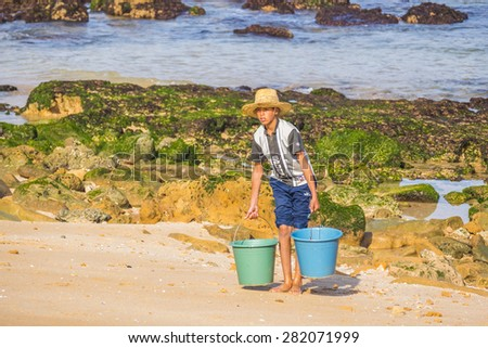 OUALIDIA, MOROCCO, APRIL 6, 2015: Boy-fisherman carries buckets with freshly caught seafood - stock photo