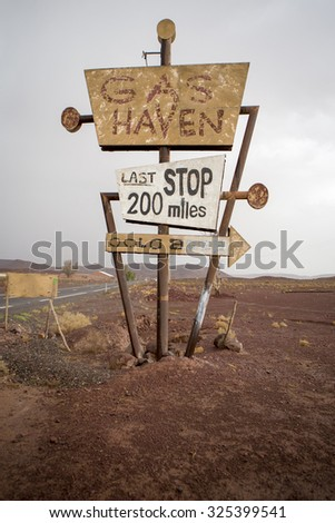 OUARZAZATE, MOROCCO, AUGUST 30: Tall vintage and abandoned gas sign standing along the deserted road to Ouarzazate in Morocco 2014 - stock photo