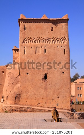 OUARZAZATE, MOROCCO - 25 February: The medieval Taourirt Kasbah built in adobe with geometrical Berber tribal symbols. Unknown Berber man in the foreground. On 25 February, 2012 - Ouarzazate, Morocco. - stock photo