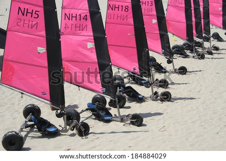 OUDDORP, THE NETHERLANDS - JULY 30TH 2013: Multiple beach sailing carts (Blokarts) with bright pink sails are standing in line on the beach in Ouddorp at the rental office on a sunny day in July. - stock photo